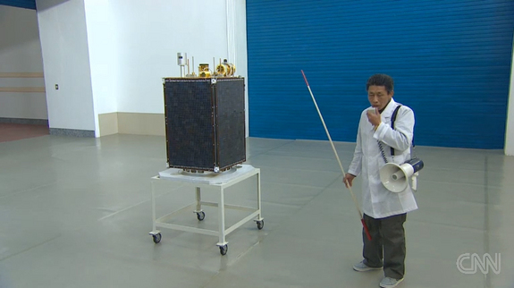 "In this still from a CNN broadcast, a North Korean official briefs reporters on the Kawngmyongsong-1 (""Bright Star 1"") satellite, which is set to launch atop the country's Unha-3 (""Galaxy-3"") rocket to launch in April 2012."