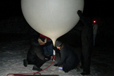 Team members fill the weather balloon with helium early in the morning of April 11, 2012, most of the way up Alaska's Murphy Dome mountain.