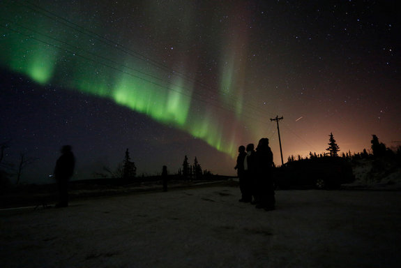 The northern lights blaze in the Alaskan sky in the early morning hours of April 11, 2012, trumping the city lights of nearby Fairbanks (at right).
