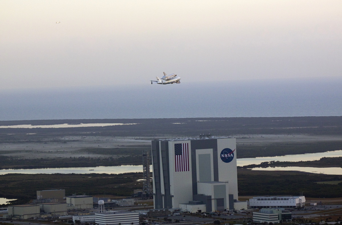 Shuttle Carrier Aircraft Carrying Discovery over Vehicle Assembly Building