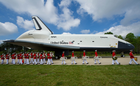 Space shuttle Enterprise is seen as the United States Marine Corp Drum and Bugle Corps and Color Guard march by at the Steven F. Udvar-Hazy Center Thursday, April 19, 2012 in Chantilly, Va