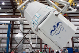 The Dragon spacecraft being rotated before it is mated to the Falcon 9 rocket in SpaceX's hangar in Cape Canaveral, FL.