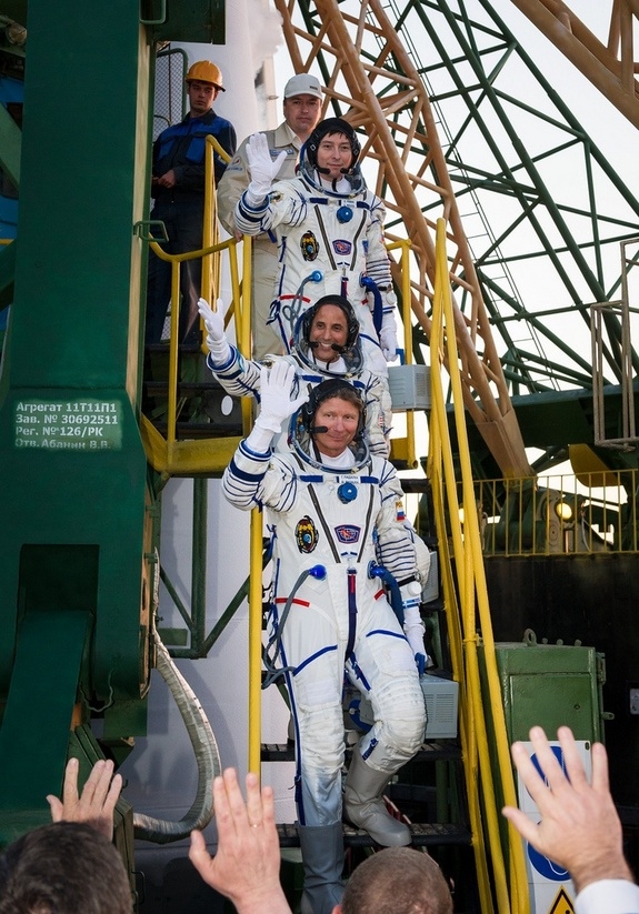 Expedition 31 Soyuz Commander Gennady Padalka (bottom), NASA flight engineer Joe Acaba and flight engineer Sergei Revin (top) wave farewell from the base of their Soyuz rocket at the Baikonur Cosmodrome in Kazakhstan shortly before launching toward the space station on May 14, 2012 (May 15 local time).