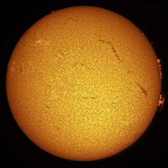 This is a typical view of the sun as seen through an H-alpha telescope. Details in the sun's chromosphere that are visible include fine, carpet-like spicules and long, dark filaments across the disk as well as delicate prominences along the edges of the sun. Paul Hyndman captured this view April 16, 2004, using an Astro-Physics 105-mm refractor fitted with a Coronado Solarmax90/T-Max and 30-mm blocking filter, a Tele Vue 2X Powermate lens and an SBIG STL-11000M CCD camera.
