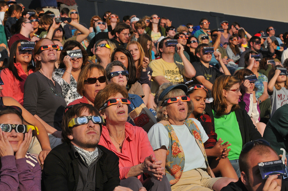 Spectators in special solar eclipse glasses stare at the sun during the annular solar eclipse on May 20, 2012. The observers attended a special event held at the University of Colorado's Folsom Field football stadium in Boulder, Colo.