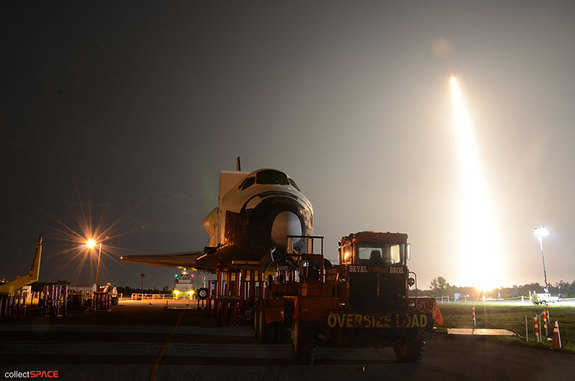 SpaceX's first space station-bound Dragon spacecraft, flying atop a Falcon 9 rocket, launches behind a high fidelity mockup of the space shuttle, NASA's previous means of delivering cargo to International Space Station. Liftoff occurred on May 22, 2012 from Cape Canaveral Air Force Station.
