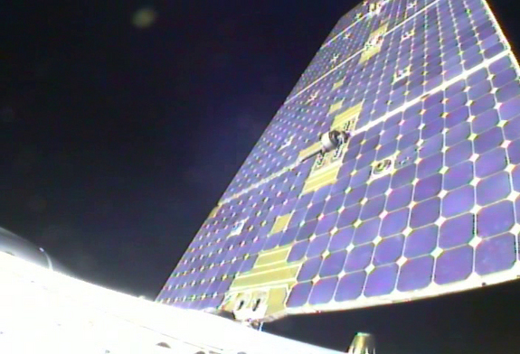 View from SpaceX's Dragon spacecraft looking outward at one of two solar array panels in the process of deploying after launch on May 22, 2012.