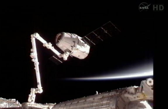 Dragon capsule attached to the Canadarm2 floats with the Earth's limb in the background, May 25, 2012.