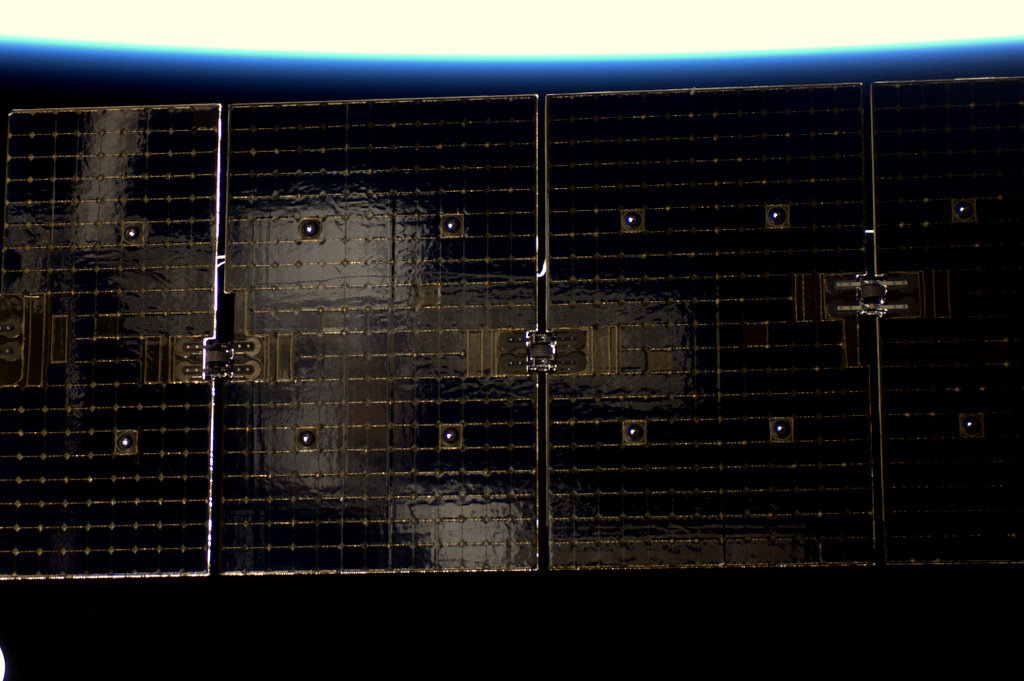 Soyuz Reflected in one of Dragon's Solar Panels