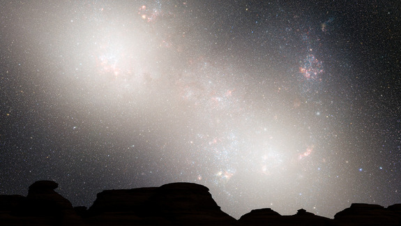 During the second close passage, the cores of the Milky Way and Andromeda appear as a pair of bright lobes. Star-forming nebulae are much less prominent because the interstellar gas and dust has been significantly decreased by previous bursts of star formation. Image released May 31, 2012.