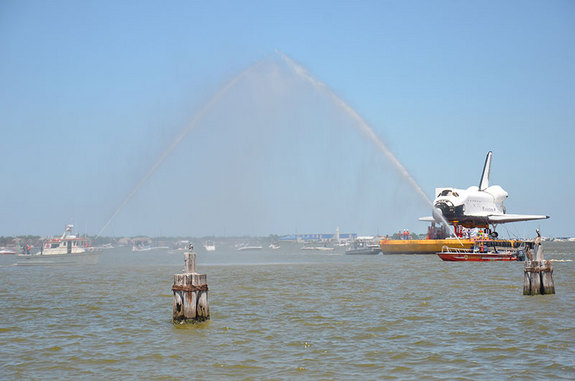 Houston fire boats offer a welcome salute to a space shuttle replica that arrived at the city's Clear Lake dock for delivery to Space Center Houston for public display on June 1, 2012.