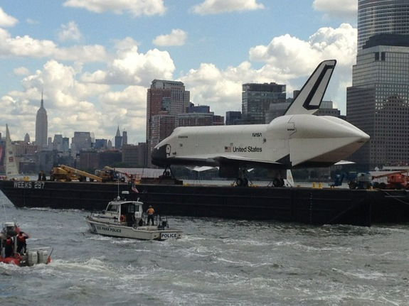 NASA's space shuttle Enterprise sails up New York City's Hudson River with the Empire State Building in the background while en route to its new home, the Intrepid Sea, Air and Space Museum on June 6, 2012.