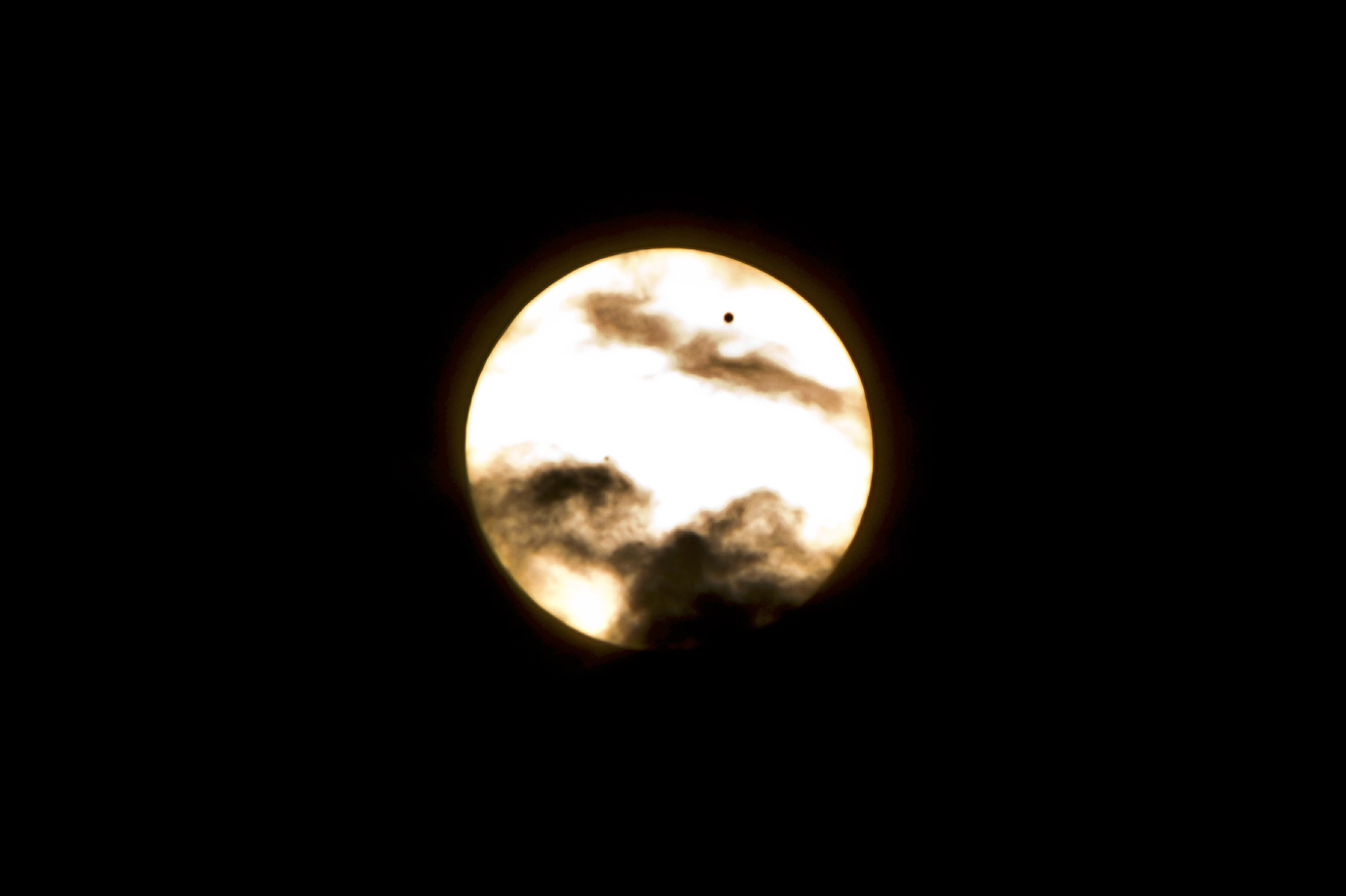 Venus Crossing the Sun in the Clouds