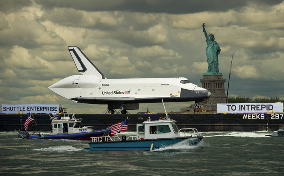 Atop a barge on Wednesday, June 6, 2012, the space shuttle Enterprise was towed on the Hudson River past the Statue of Liberty on its way to the Intrepid Sea, Air and Space Museum, where it will be permanently displayed.