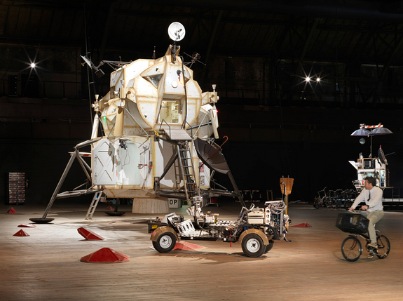 "Installation view of the Landing Excursion Module (LEM), Mars Excursion Roving Vehicle (MERV), and Tom Sachs on WAR Bike in ""Space Program: Mars."""