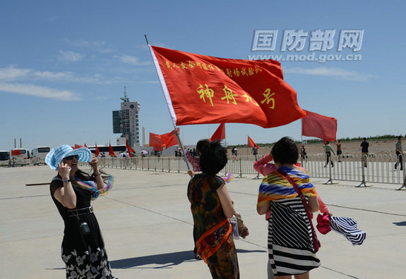 Crowds wave the Chinese flag as a Chinese Long March 2F rocket carrying the Shenzhou 9 spacecraft rolls out to the launch pad at Jiuquan Satellite Launch Center in northwest China on June 9, 2012.
