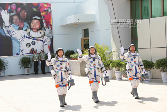 The three astronauts of China's Shenzhou 9 crew, the fourth human spaceflight for the country, wave to cheering supporters as they walk out to their Shenzhou 9 spacecraft before launching on June 16, 2012, from the Jiuquan Satellite Launch Center. The crew is Liu Yang, China's first female astronaut (left); Jing Haipeng, mission commander (center);and Liu Wang.