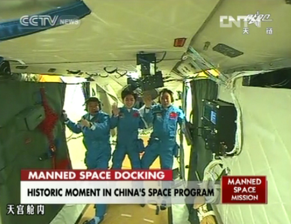 The crew of China's Shenzhou 9 mission waves to a camera aboard the Tiangong 1 space module after successfully docking their capsule at the test module on June 18, 2012, in this still from a state-run TV broadcast on CNTV The crew is (from left) Liu Wang, Liu Yang (China's first female astronaut), and mission commander Jing Haipeng.