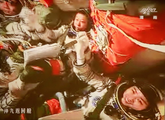 The three astronauts aboard China's Shenzhou 9 spacecraft grasp hands to celebrate their successful manned docking with the Tiangong 1 orbiting module on June 24, 2012. At center is astronaut Liu Wang, who piloted the successful docking. Mission commander Jing Haipeng is at left with astronaut Liu Yang, China's first female astronaut, at right.
