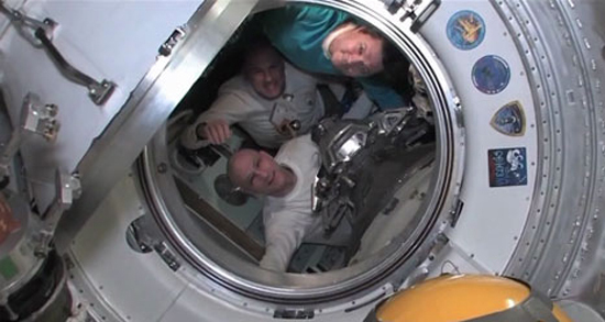 Expedition 31 commander Oleg Kononenko of Russia (top), Dutch astronaut Andrew Kuipers (center) and NASA astronaut Don Pettit bid farewell to their crewmates on the International Space Station just before shutting the hatches between their Soyuz and the station for a July 1, 2012, return to Earth.
