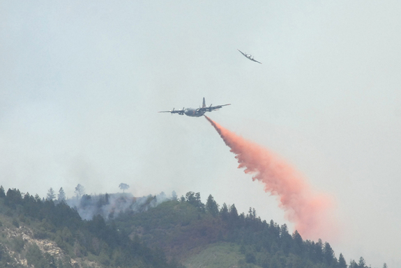 A U.S. Forest Service aircraft breaks away, top, as a Modular Airborne Firefighting System-equipped C-130 aircraft begins dropping flame retardant on a section of the Waldo Canyon fire near Colorado Springs, Colo., on June 26, 2012.