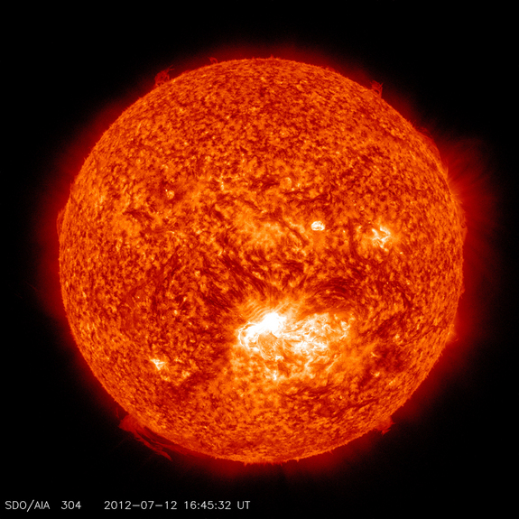 This image from the Solar Dynamics Observatory (SDO) shows the sun at 12:45 PM EDT on July 12, 2012 during an X1.4 class flare. The image is captured in the 304 Angstrom wavelength, which is typically colorized in red and shows temperatures in the 50,000 Kelvin range.