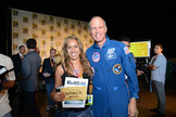 "XCOR Chief Test Pilot/former NASA Astronaut Richard Searfoss (right) and Mercedes Becerra (left) of Paso Robles, Calif., winner of the trip to space given away at ""The Big Bang Theory"" panel at Comic-Con on July 13, 2012."