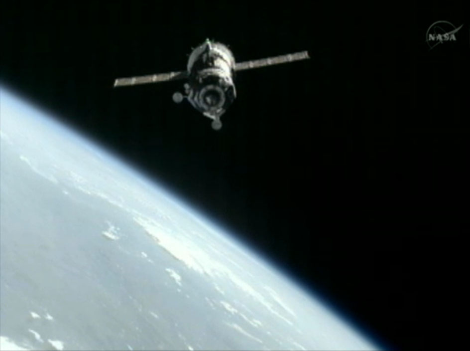 Soyuz Capsule Docks at Space Station with International Space Crew