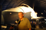 Fred Haise, Jr., veteran NASA astronaut, answers a reporter's questions with shuttle Enterprise in the background at the new Intrepid Museum exhibit. Photo taken July 18, 2012.