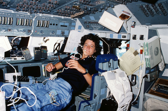 Floating freely on the flight deck, Sally Ride communicates with ground controllers in Houston during her STS-7 mission in June 1983.