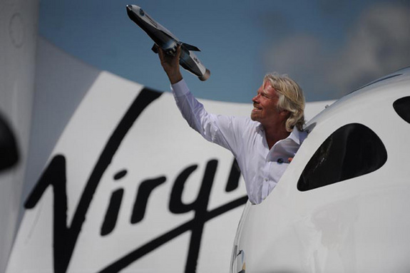 Sir Richard Branson hangs out a window of his full size SpaceShipTwo replica holding a scale model of LauncherOne.