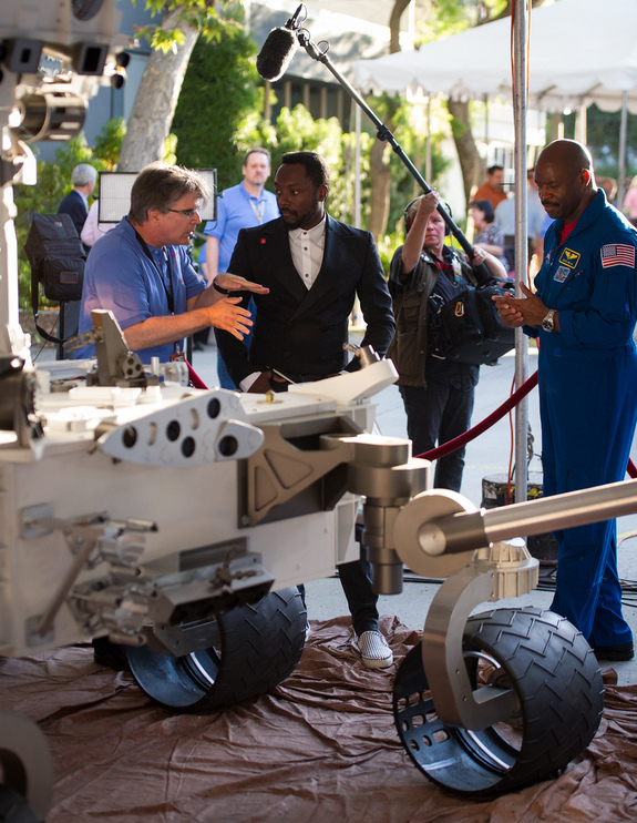 Musician Will.i.am, center, listens to NASA scientist Jim Garvin of the Goddard Space Flight Center talk next to a mock up of the Mars Science Laboratory rover Curiosity as astronaut Leland Melvin looks on at the Jet Propulsion Laboratory (JPL) a few hours ahead of the planned landing of the Curiosity rover on Mars, Sunday, Aug. 5, 2012 in Pasadena, Calif.