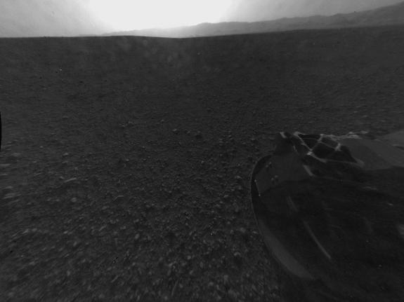 "This full-resolution version of one of the first images taken by a rear-left Hazard-Avoidance camera on NASA's Curiosity rover, was released on Aug. 6, 2012.The image was originally taken through the ""fisheye"" wide-angle lens, but has been ""linearized"" so that the horizon looks flat rather than curved. Part of the rim of Gale Crater can be seen from the top-middle to the top-right of the image, and one of the rover's wheels is pictured at the bottom right."