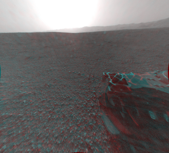 This image is a 3-D view behind NASA's Curiosity rover, which landed on Mars on Aug. 5 PDT (Aug. 6 EDT). The anaglyph was made from a stereo pair of Hazard-Avoidance Cameras on the rear of the rover and released Aug. 7.