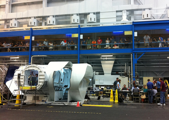 "The 2012 RATS team prepares for mission start in JSC's Building 9, with the prototype second-generation space exploration vehicle on the left and spectators in the overhead ""catwalk."""