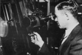 Clyde Tombaugh, discoverer of Pluto, peers into an instrument.