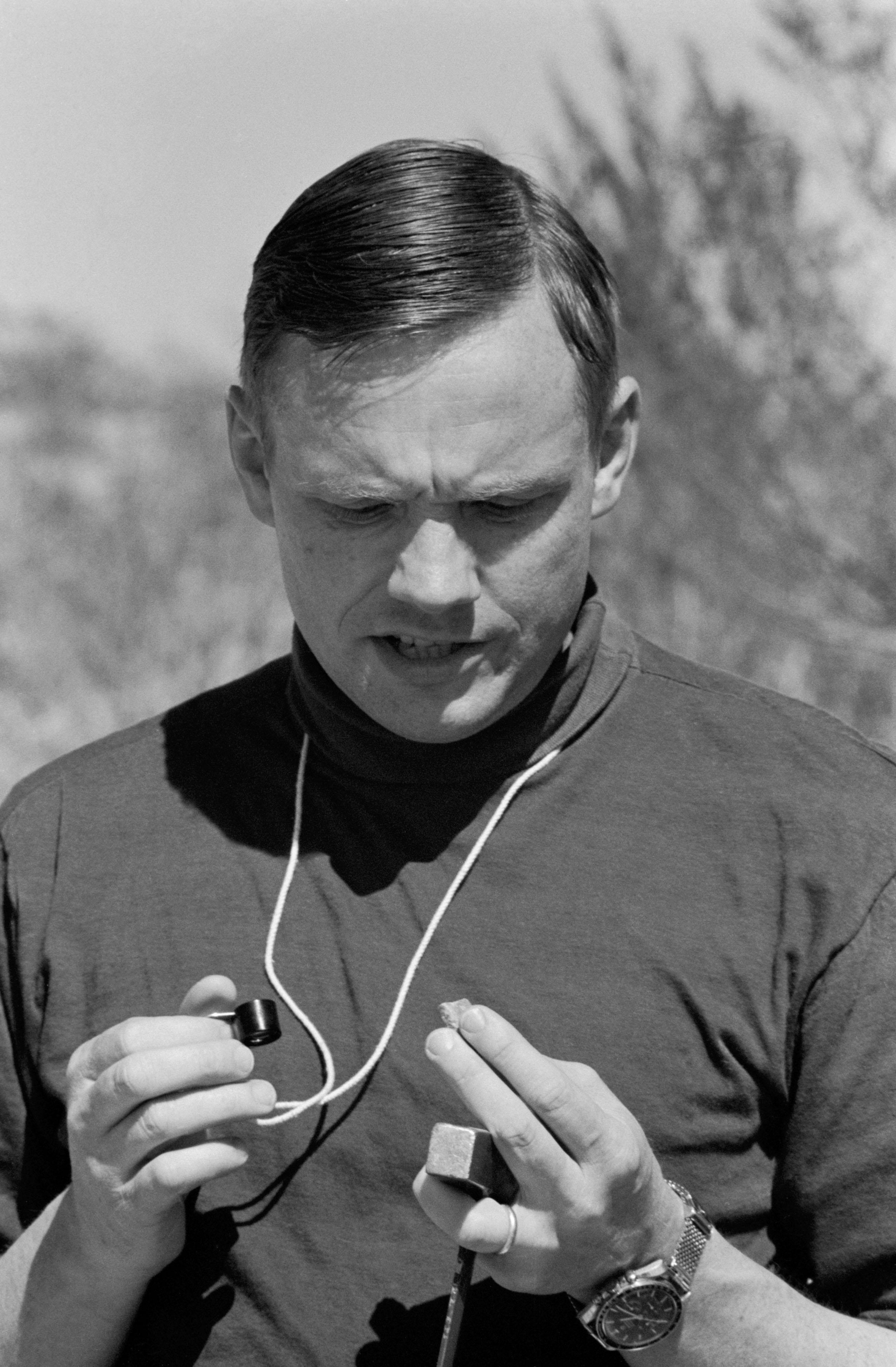Neil Armstrong Studies Rock Sample