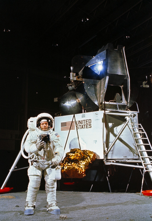 Astronaut Neil A. Armstrong, wearing an Extravehicular Mobility Unit, participates in a simulation of deploying and using lunar tools on the surface of the moon during a training exercise in Building 9 on April 22, 1969. Armstrong is the commander of the Apollo 11 lunar landing mission. In the background is a Lunar Module mock-up.