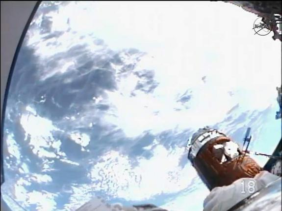 A view of Earth below from the helmet camera of Japanese spacewalker Akihiko Hoshide on Aug. 30, 2012. The gold, cylindrical spacecraft parked to the right in the photo is the Japanese robotic HTV-3 cargo freighter.