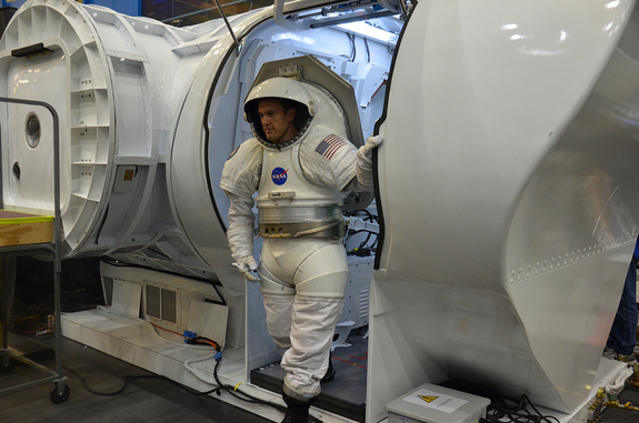 David Coan, wearing a Mark III spacesuit, exits NASA's multi-mission Space Exploration Vehicle (SEV) during an asteroid mission simulation at the Johnson Space Center in Houston, Aug. 30, 2012.