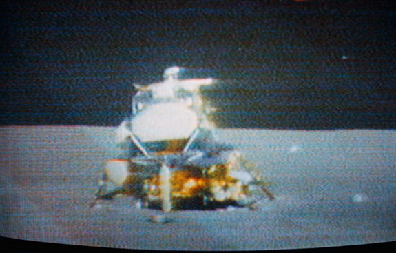 The Apollo 15 lunar module Falcon is seen only seconds before ascent stage liftoff in this color reproduction taken from a transmission made by the television camera mounted on the lunar roving vehicle, which was parked about 300 feet east of the LM.