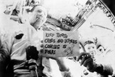 "Apollo 7 astronauts Walter M. Schirra Jr. (on right) and Donn F. Eisele are seen in the first live television transmission from space. Schirra is holding a sign that reads, ""Keep those cards and letters coming in, folks!"""