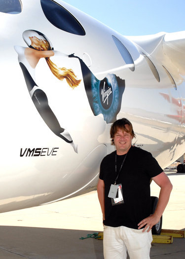Canadian John Criswick poses for a photo with Virgin Galactic's WhiteKnightTwo Eve, the carrier aircraft that will launch the SpaceShipTwo spaceliner into suborbital space during his spaceflight.