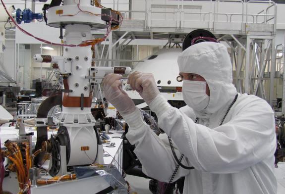 In this image, the technician's hands are just below one of the two REMS (Remote Environmental Monitoring Station) booms. The other boom extends to the left a little farther up the mast. This photo was taken during installation of the REMS instrument in September 2011, inside a clean room at NASA's Jet Propulsion Laboratory in Pasadena, Calif.