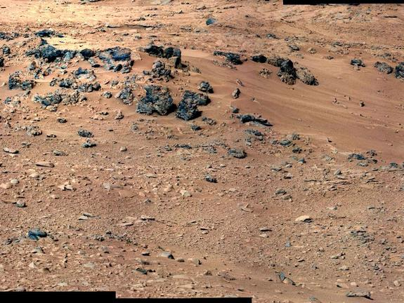 "This patch of windblown sand and dust downhill from a cluster of dark rocks is the ""Rocknest"" site, which has been selected as the likely location for first use of the scoop on the arm of NASA's Mars rover Curiosity. This view is a mosaic of images taken by the telephoto right-eye camera of the Mast Camera (Mastcam) during the 52nd Martian day, or sol, of the mission (Sept. 28, 2012), four sols before the rover arrived at Rocknest."