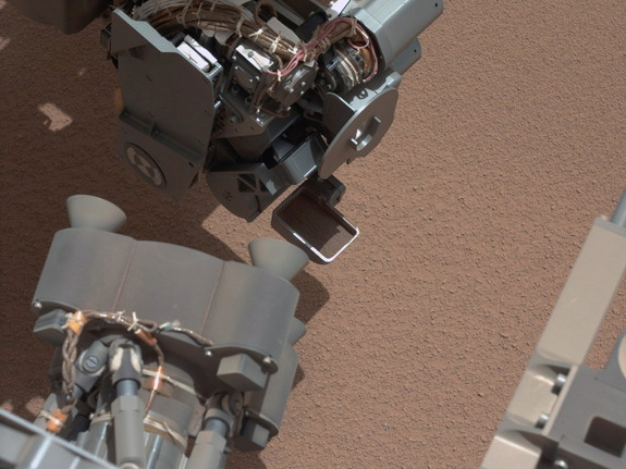 This image from the right Mast Camera (Mastcam) of NASA's Mars rover Curiosity shows a scoop full of sand and dust lifted by the rover's first use of the scoop on its robotic arm. In the foreground, near the bottom of the image, a bright object is visible on the ground. The object might be a piece of rover hardware. This image was taken during the mission's 61st Martian day, or sol (Oct. 7, 2012).