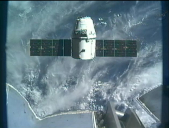 SpaceX's Dragon space capsule hovers just below the International Space Station's robotic arm in this view from an arm camera on Oct. 10, 2012, during the CRS-1 commercial cargo mission.