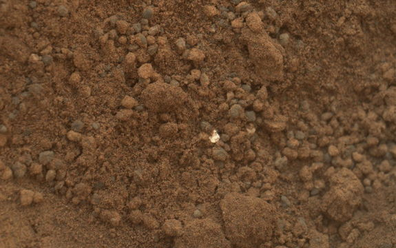 "This image shows part of the small pit or bite created when NASA's Mars rover Curiosity collected its second scoop of Martian soil at a sandy patch called ""Rocknest."" This image was taken by the Mars Hand Lens Imager (MAHLI) camera on Curiosity's arm during the 69th Martian day, or sol, of the mission (Oct. 15, 2012)."