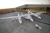 "Virgin Galactic's first SpaceShipTwo suborbital spaceliner (center) is seen mated to its WhiteKnightTwo mothership in front of the ""Faith"" hangar at The Spaceship Company during a dedication ceremony in Mojave, Calif."