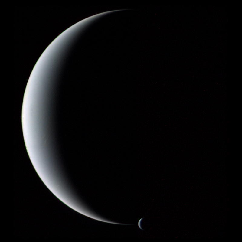 The crescent planet Neptune and its crescent moon Triton
